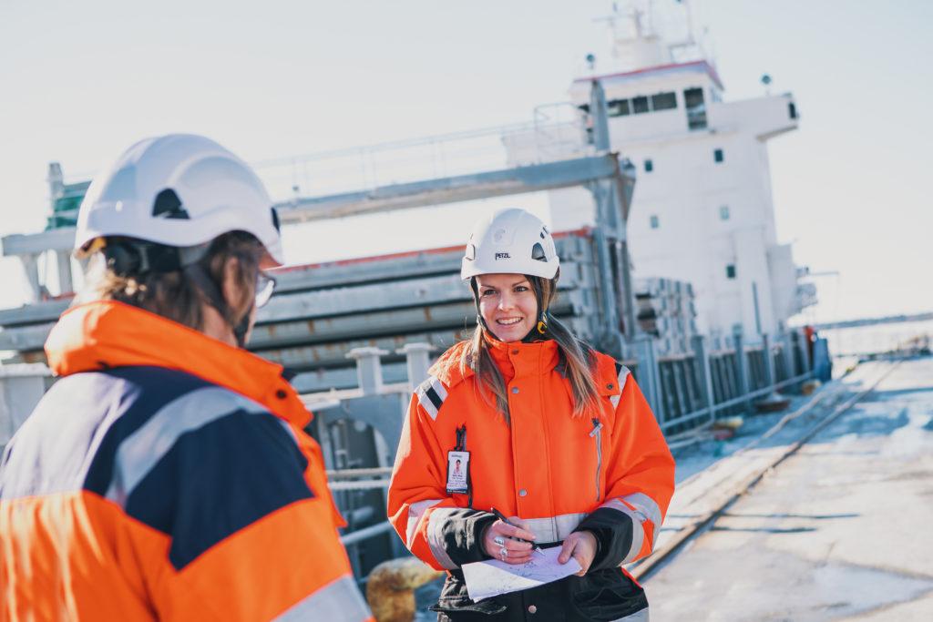 Laivan edessä seiroo oranssitakkisia KWH Logisticsin työntekijöitä.